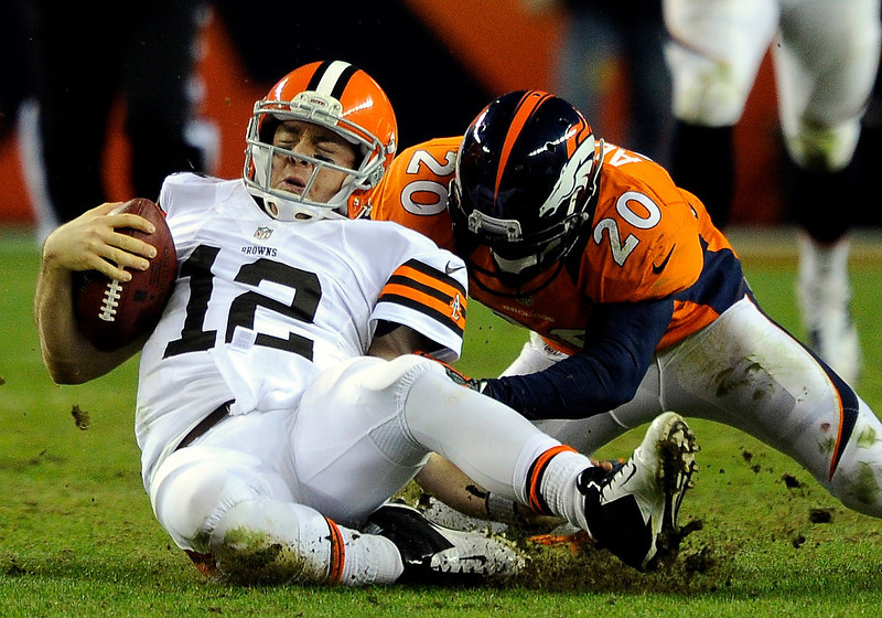 . Denver Broncos strong safety Mike Adams (20) tackles Cleveland Browns quarterback Colt McCoy (12) during the fourth quarter. The Denver Broncos vs Cleveland Browns at Sports Authority Field Sunday December 23, 2012. Tim Rasmussen, The Denver Post