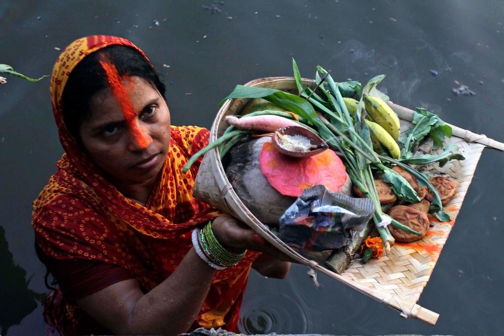 . A Hindu woman devotee performs rituals during the Chhath Puja festival at a lake in Kolkata, India, Friday, Nov. 8, 2013.   (AP Photo/Bikas Das)