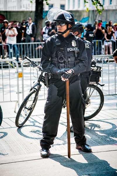 A Seattle police officer stands at the ready with a big ass stick.