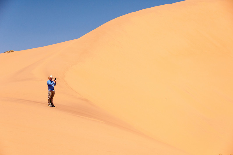 Man taking photos of sand dunes of Namib Desert