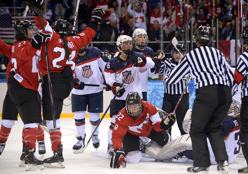 . Canada\'s Natalie Spooner (2nd L) celebrates with team mates after scoring a goal during the Women\'s Ice Hockey Group A match between Canada and USA at the Sochi Winter Olympics on February 12, 2014 at the Shayba Arena. AFP PHOTO / ALEXANDER NEMENOV/AFP/Getty Images