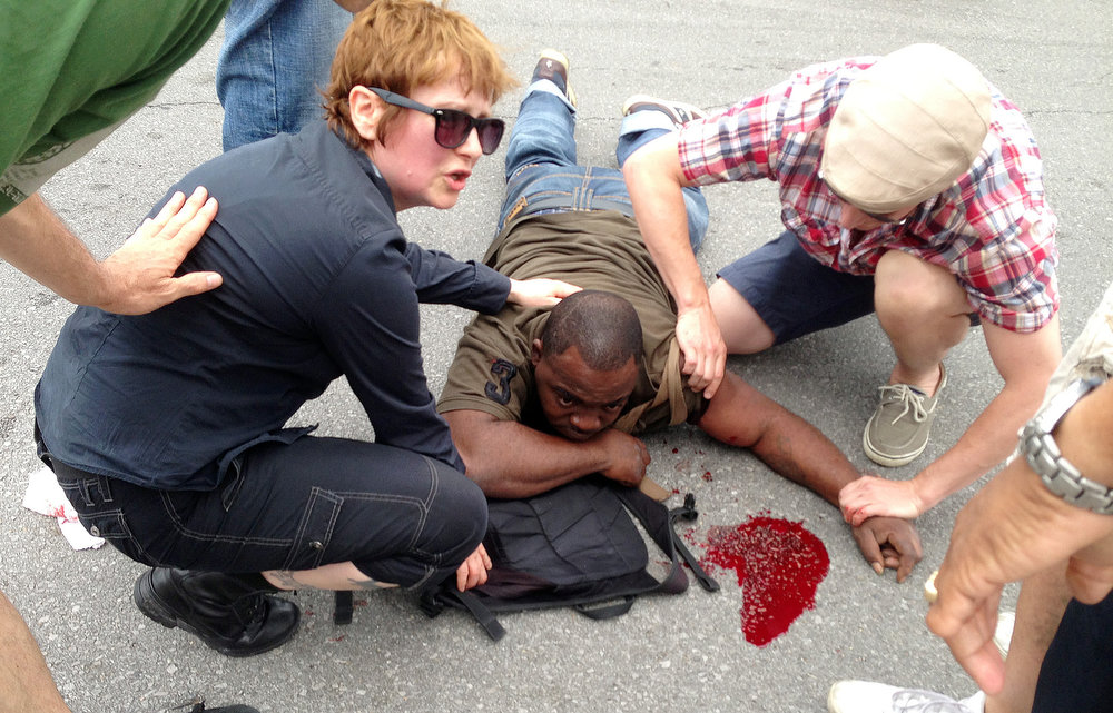 . Bystanders comfort a shooting victim while awaiting EMS at the intersection of Frenchmen and N. Villere Streets after authorities say gunfire injured at least a dozen people, including a child, at a Mother\'s Day second-line parade in New Orleans on Sunday, May 12, 2013. No deaths were reported. (AP Photo/The Times-Picayune, Lauren McGaughy)