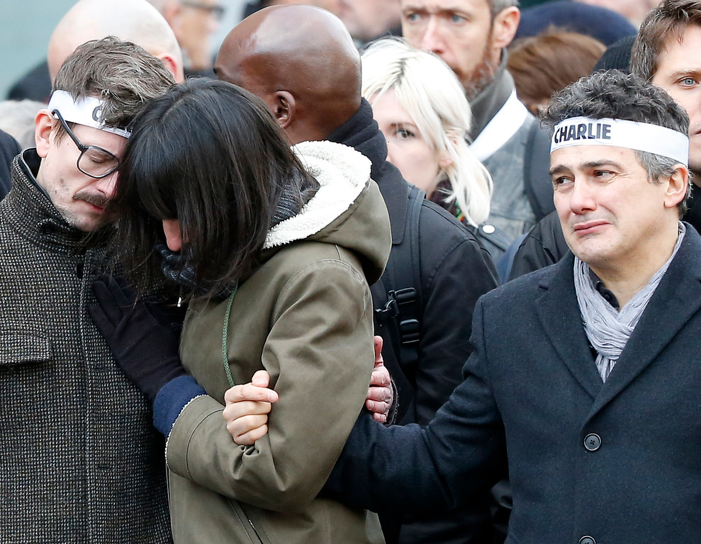 . Charlie Hebdo newspaper staff, with editorialist Patrick Pelloux, right, cartoonist Renald Luzier, known as Luz, left, react during a march in Paris, France, Sunday, Jan. 11, 2015.  Thousands of people began filling France�s iconic Republique plaza, and world leaders converged on Paris in a rally of defiance and sorrow on Sunday to honor the 17 victims of three days of bloodshed that left France on alert for more violence. (AP Photo/Michel Euler)