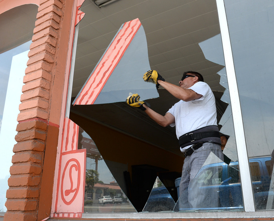 . Martin Jimenez cleans up broken glass from a front window of a former tile store after the 5.1 earthquake centered in La Habra on Saturday March 29, 2014. (Staff Photo by Keith Durflinger/Whittier Daily News)