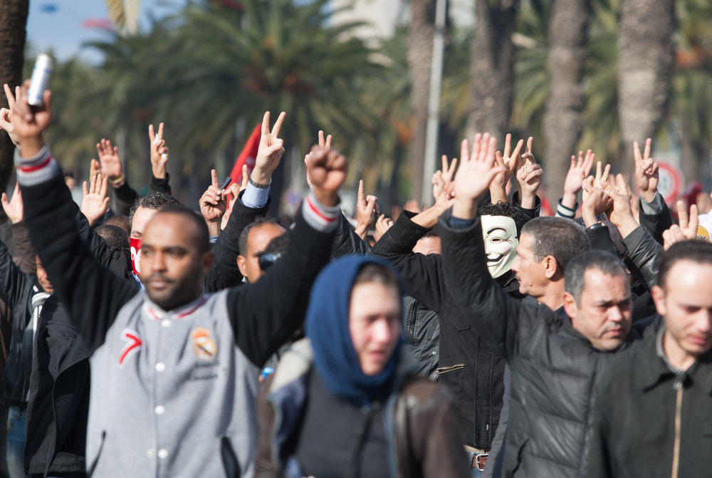 Description of . Demonstrators raise their hands to protest the killing of opposition leader Chokri Belaid in Tunis, Wednesday, Feb. 6, 2013. The Tunisian opposition leader critical of the Islamist-led government and violence by radical Muslims was shot to death Wednesday,  the first political assassination in post-revolutionary Tunisia. The killing is likely to heighten tensions in the North African nation whose path from dictatorship to democracy so far has been seen as a model for the Arab world. (AP Photo/Amine Landoulsi)