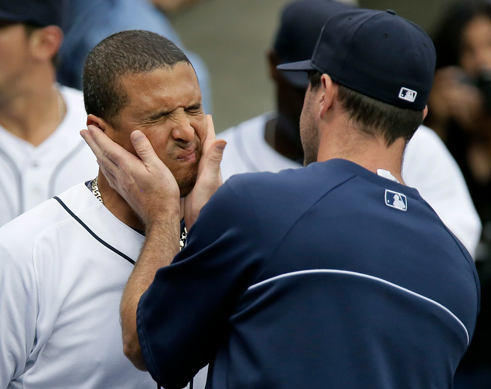. Detroit Tigers\' Victor Martinez receives light slaps to the cheeks from pitcher Justin Verlander before a baseball game against the Seattle Mariners Saturday, Aug. 16, 2014, in Detroit. The Tigers won 4-2. (AP Photo/Duane Burleson)