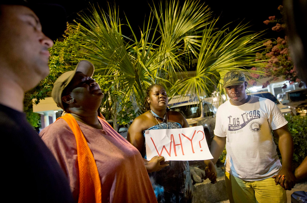 . Surreace Cox, of North Charleston, S.C., holds a sign during a prayer vigil down the street from the Emanuel AME Church early Thursday, June 18, 2015, following a shooting Wednesday night in Charleston, S.C. (AP Photo/David Goldman)