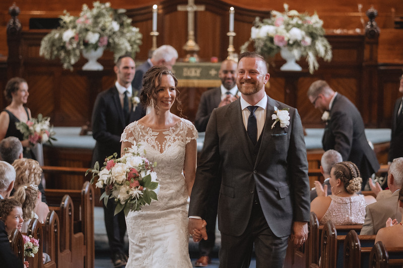 The bride and groom smiling as they walk hand and hand up the isle as everyone claps and is smiling towards them.
