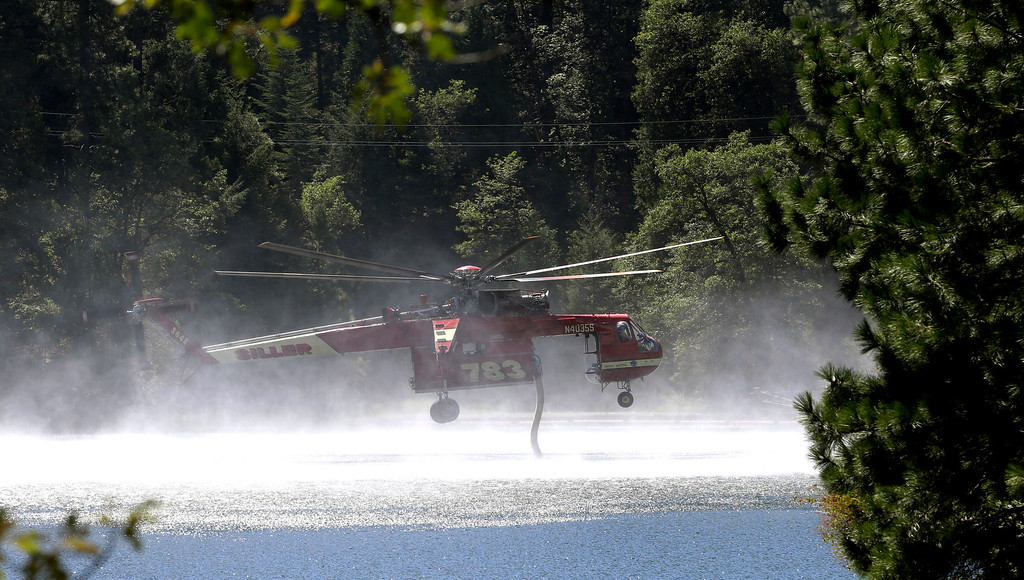 . A Skycrane helicopter refills its tanks with water to battle the King Fire near Pollack Pines, Calif., Monday, Sept. 15, 2014. The fire, which started Sunday has consumed more than 3,000 acres and forced the evacuation of dozens of homes.(AP Photo/Rich Pedroncelli)