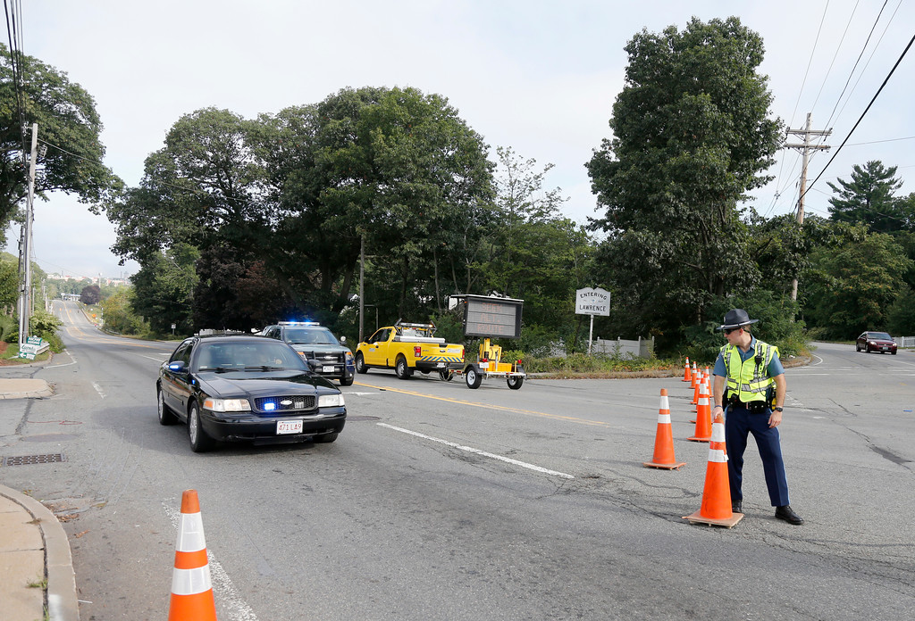 . A member of the State Police moves a cone for an emergency vehicle at a road block on Route 114 in North Andover, Mass., at the Lawrence city line, Friday, Sept. 14, 2018. Many roads remain closed after Thursday afternoon gas explosions and fires triggered by a problem with a gas line that feeds homes in several communities north of Boston. (AP Photo/Mary Schwalm)