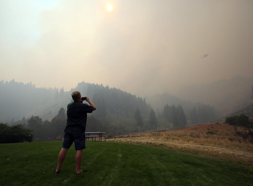 . John Larson photographs a helicopter dropping retardant on the Elk Complex behind his home in Pine, Idaho on Monday, Aug. 12, 2013. (AP Photo/The Idaho Statesman, Joe Jaszewski)