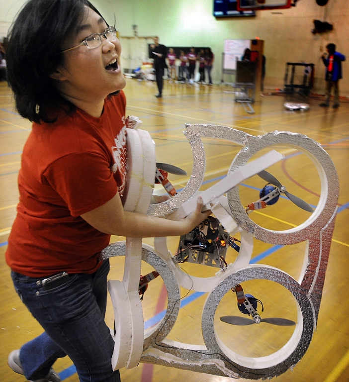 """. Mary Nguyen of Team Der Red Penguins rushes her quadcopter off the court to give the copter a new frame after the frame was destroye during a crash during  28th Annual ME72 Engineering Design Contest, \""""Sponge Wars Attack of the Drones\"""" at Caltech Brown Gym Tuesday, March 13, 2013. Mechanical Engineering 72 competition features teams maneuvering kitchen sponges into a goal with a pair of autonomous robotic vehicles � and preventing opposing teams from doing the same. Six teams  competed head-to-head in a series of rounds. The team with the most points at the end of each heat wins. The victors earn the admiration of the crowds in the stands and are honored with the ME-72 trophy. (Photo by Walt Mancini/SXCity)"""