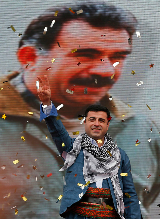. File photo of Selahattin Demirtas, co-chairman of the pro-Kurdish Peace and Democracy Party (BDP), gesturing as he stands in front of a large poster of jailed Kurdistan Workers Party (PKK)leader Abdullah Ocalan during a rally in Istanbul March 17, 2013. A top Kurdish politician said April 15, 2013, it would be difficult for Kurdish fighters to disarm before leaving Turkey under a peace process, stressing that the key issue was that they depart peacefully without contact with the Turkish military. Prime Minister Tayyip Erdogan\'s government is seeking a weapons-free pullout by militants of the PKK as part of a drive to end a three-decades long conflict which has killed more than 40,000 people. REUTERS/Murad Sezer/Files