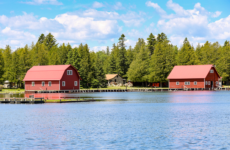 two red barns sitting lakeside