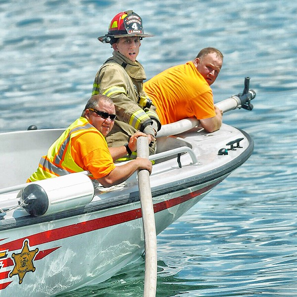 Jack Haley/Messenger Post MediaFirefighters look for water after repositioning the boat. The pressure from the fire hose pushed the boat that was on fire away from them.