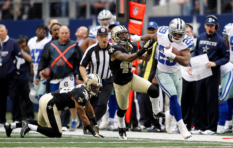 . Dallas Cowboys running back DeMarco Murray runs past New Orleans Saints corner back Elbert Mack and corner back Johnny Patrick in the second half of their NFL football game in Arlington, Texas December 23, 2012.  REUTERS/Mike Stone
