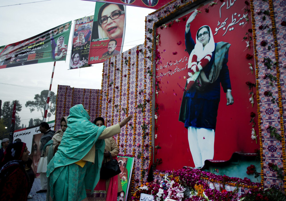 Description of . A supporters of Pakistan's assassinated leader Benazir Bhutto throws rose petals at a picture of her to pay tribute on her fifth anniversary in Rawalpindi, Pakistan,  Thursday, Dec. 27, 2012. The 24-year-old son of former Pakistani Prime Minister Benazir Bhutto has launched his political career at his ancestral place Larkana, with a fiery speech on the fifth anniversary of his mother's assassination. (AP Photo/B.K. Bangash)