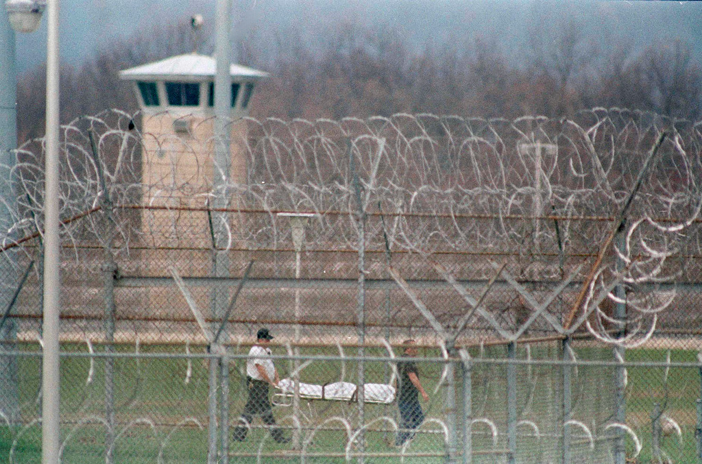 . The body of the seventh prisoner killed at a riot at Southern Ohio Correctional Facility in Lucasville, Ohio, is removed by law enforcement authorities, April 13, 1993.  Eight guards have been taken hostage at the prison.  (AP Photo/Chris Kasson)