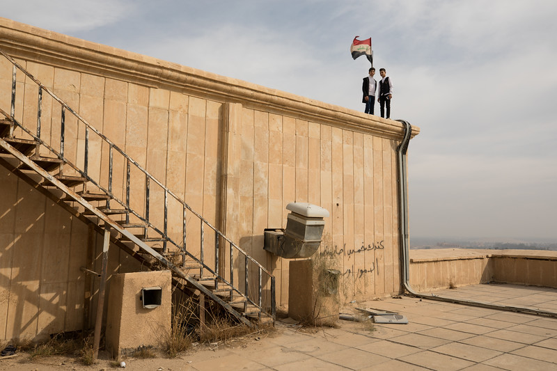 A couple of teenagers posing beside the flag of Iraq on the palace roof.