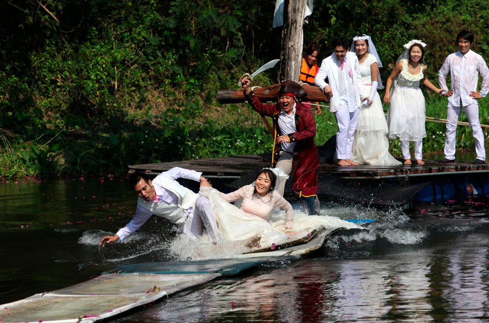 Description of . Thai groom and bride, Sorawich Changtor (front L), 28, and Rungnapa Panla (front R), 30, run to escape a man dressed as a pirate as (behind L-R) Prasit Rangsiyawong, 29, Varuttaon Rangsiyawong, 27, Chutima Imsuntear, 37, and Sopon Sapaotong, 41, look on during a wedding ceremony ahead of Valentine's Day in Prachin Buri province, east of Bangkok February 13, 2013. Three Thai couples took part in the wedding ceremony arranged by a Thai resort that aimed to strengthen the relationships of the couples by doing fun activities.  REUTERS/Kerek Wongsa