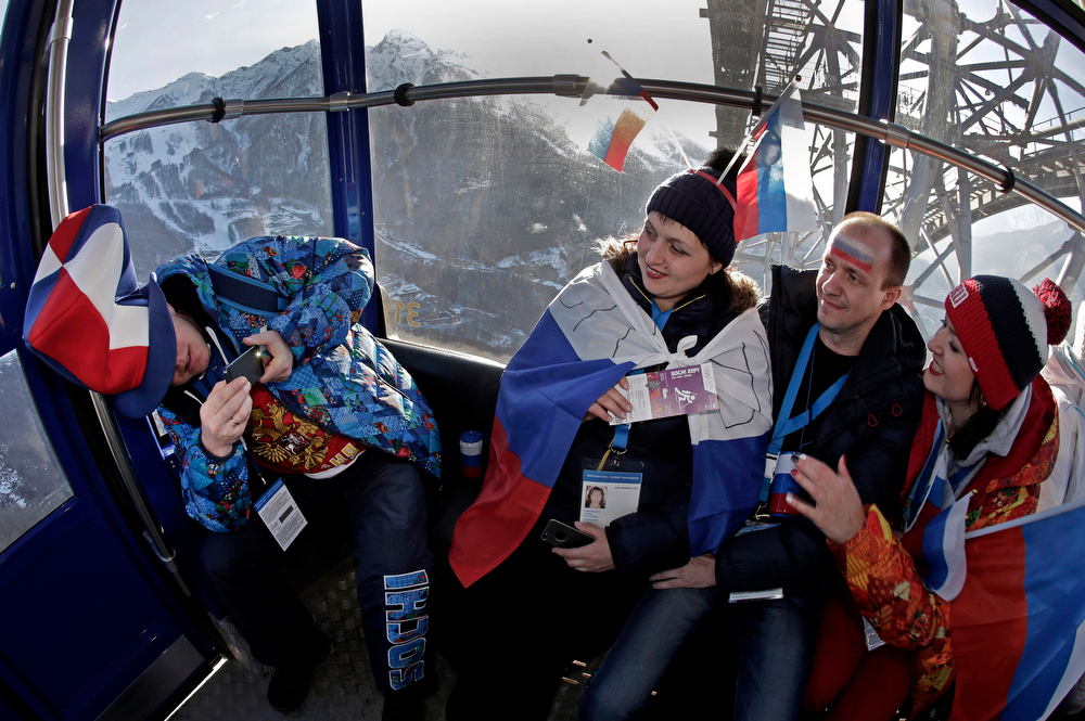 . Fans take photos during a cable car ride to the men\'s biathlon 10k sprint, at the 2014 Winter Olympics, Saturday, Feb. 8, 2014, in Krasnaya Polyana, Russia. (AP Photo/Charlie Riedel)