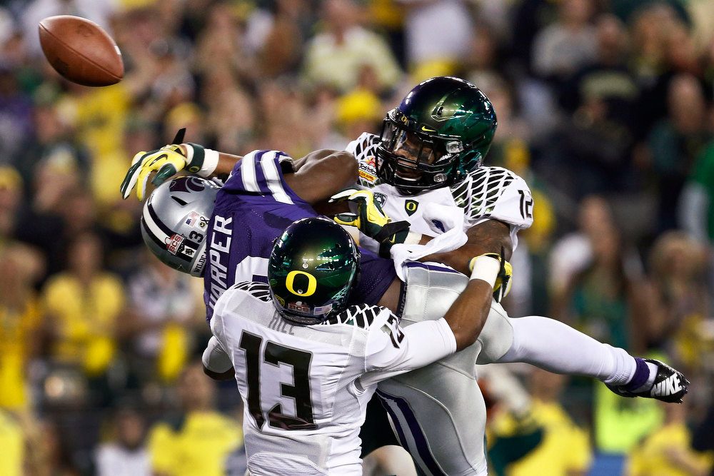 Description of . Oregon's Brian Jackson (12) and Troy Hill (13) break up a pass intended for Kansas State's Chris Harper during the first half in the Fiesta Bowl NCAA college football game, Thursday, Jan. 3, 2013, in Glendale, Ariz.(AP Photo/Ross D. Franklin)