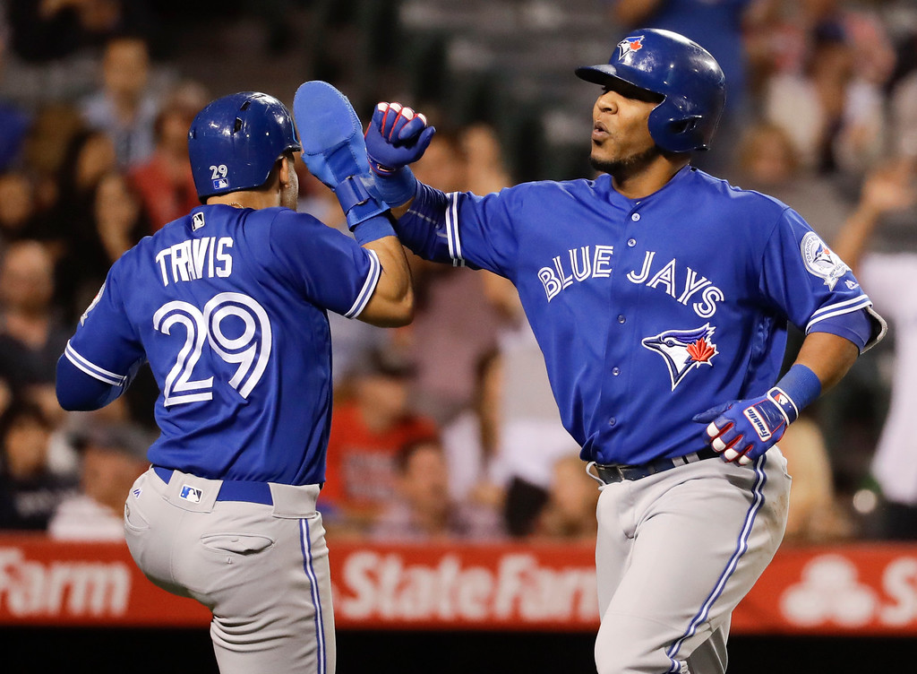 . Toronto Blue Jays\' Edwin Encarnacion, right, celebrates with Devon Travis after his two-run home run against the Los Angeles Angels during the ninth inning of a baseball game in Anaheim, Calif., Friday, Sept. 16, 2016. (AP Photo/Chris Carlson)