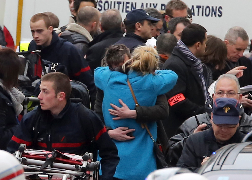. People hug each other outside the French satirical newspaper Charlie Hebdo\'s office, in Paris, Wednesday, Jan. 7, 2015. Masked gunmen stormed the offices of a French satirical newspaper Wednesday, killing at least 11 people before escaping, police and a witness said. The weekly has previously drawn condemnation from Muslims. (AP Photo/Remy de la Mauviniere)