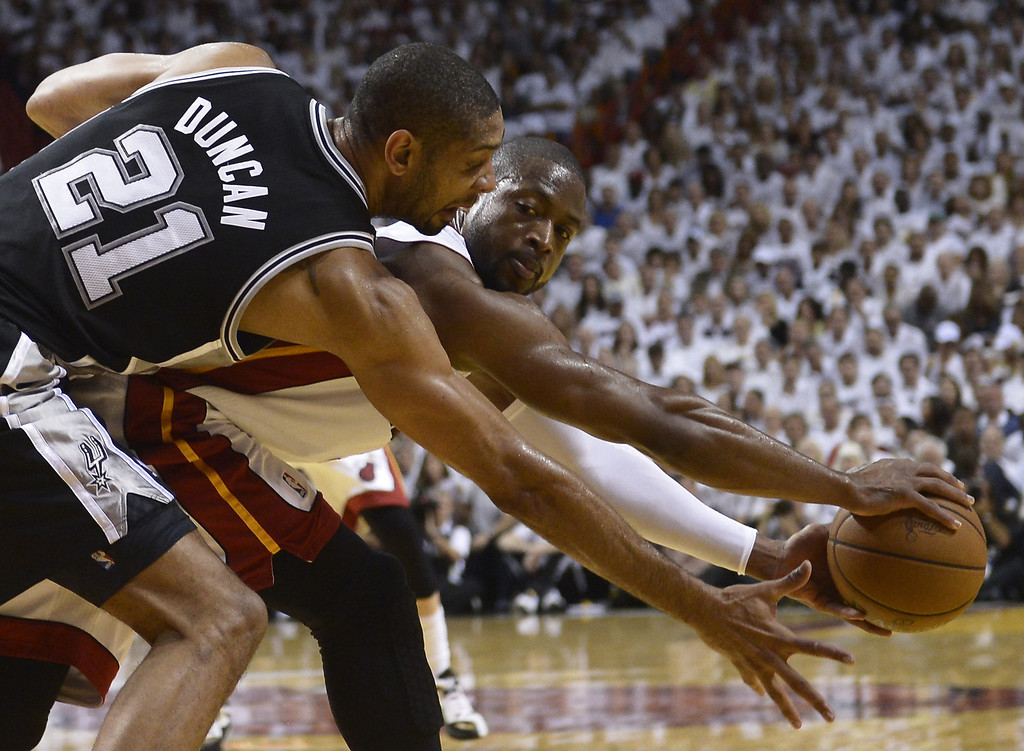 . Dwyane Wade (R) of the Miami Heat is guarded by Tim Duncan (L) of  the San Antonio Spurs in the first half during Game 7 of the NBA Finals at the American Airlines Arena June 20, 2013 in Miami, Florida.      BRENDAN SMIALOWSKI/AFP/Getty Images