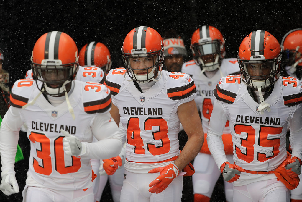 . Cleveland Browns\' Jason McCourty (30) from left, Kai Nacua (43) and Darius Jackson (35) take the field in the snow before an NFL football game against the Chicago Bears in Chicago, Sunday, Dec. 24, 2017. (AP Photo/Charles Rex Arbogast)