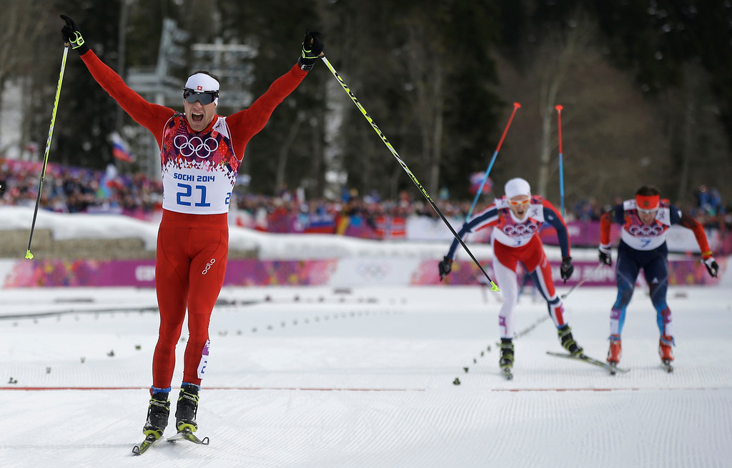 . Switzerland\'s Dario Cologna celebrates winning the gold medal as Norway\'s Martin Johnsrud Sundby, 2nd right, and Russia\'s Maxim Vylegzhanin are to cross the line during the men\'s cross-country 30k skiathlon at the 2014 Winter Olympics, Sunday, Feb. 9, 2014, in Krasnaya Polyana, Russia. (AP Photo/Gregorio Borgia)