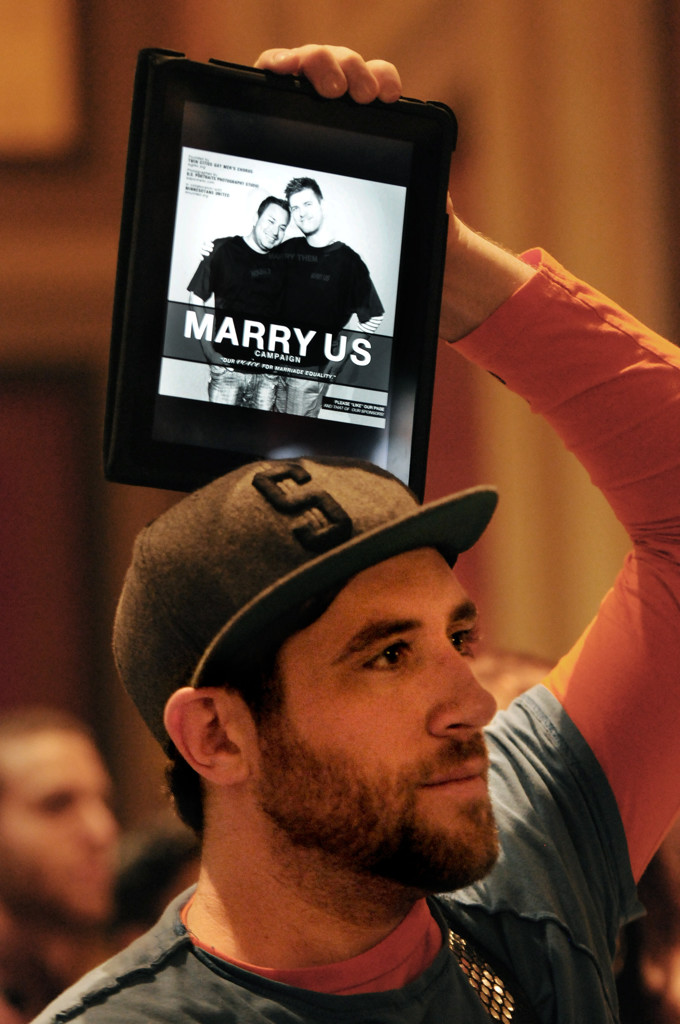 . Brent Dundore of Minneapolis holds his tablet over his head as he watches a screen showing the same-sex marriage bill debate on the House floor. (Pioneer Press: Jean Pieri)