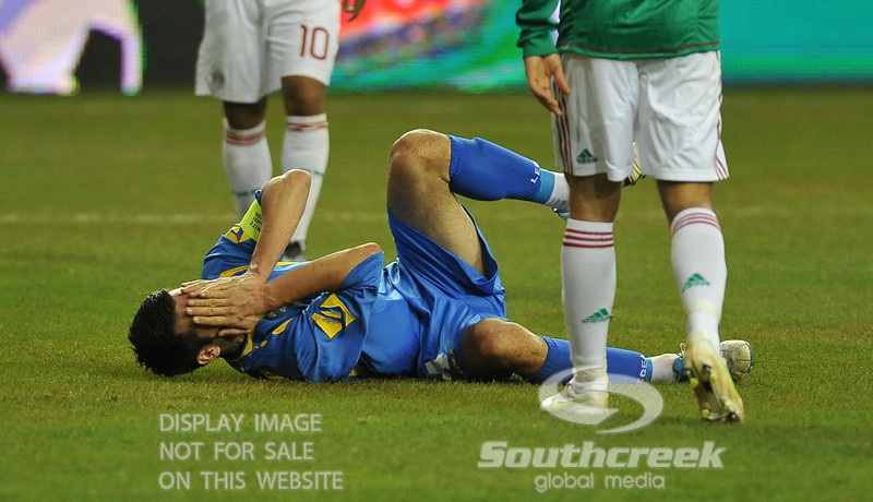 Bosnia-Herzegovina's Defencer Emir Spahic (#4) holds his hands over his face after being poked in the eye in Soccer action between Bosnia-Herzegovina and Mexico.  Mexico defeated Bosnia-Herzegovina 2-0 in the game at the Georgia Dome in Atlanta, GA.