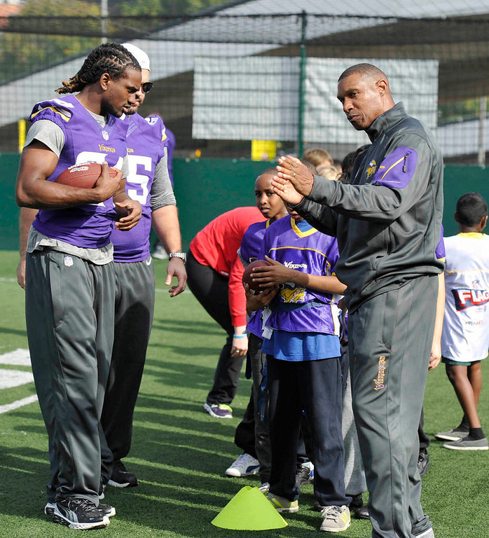 . Vikings head coach Leslie Frazier, right, and Cordarrelle Patterson participate in a youth football clinic. (NFL: Sean Ryan)