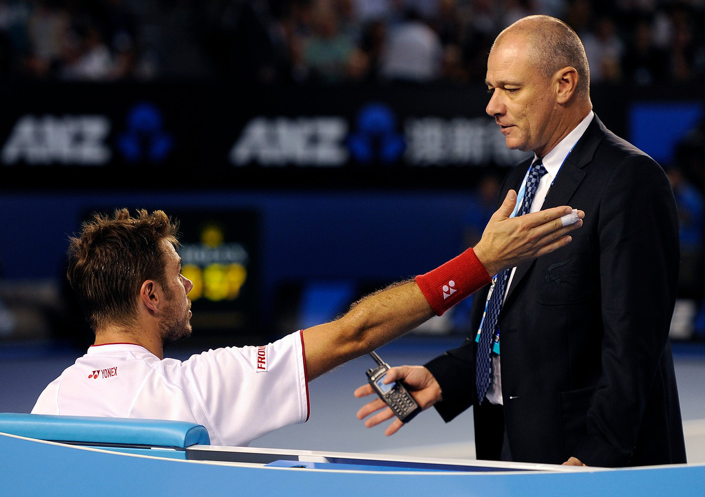 . Stanislas Wawrinka of Switzerland, left, talks with tournament referee Wayne McKewen as Rafael Nadal of Spain takes an injury time out  in the men\'s singles final at the Australian Open tennis championship in Melbourne, Australia, Sunday, Jan. 26, 2014.  (AP Photo/Andrew Brownbill)