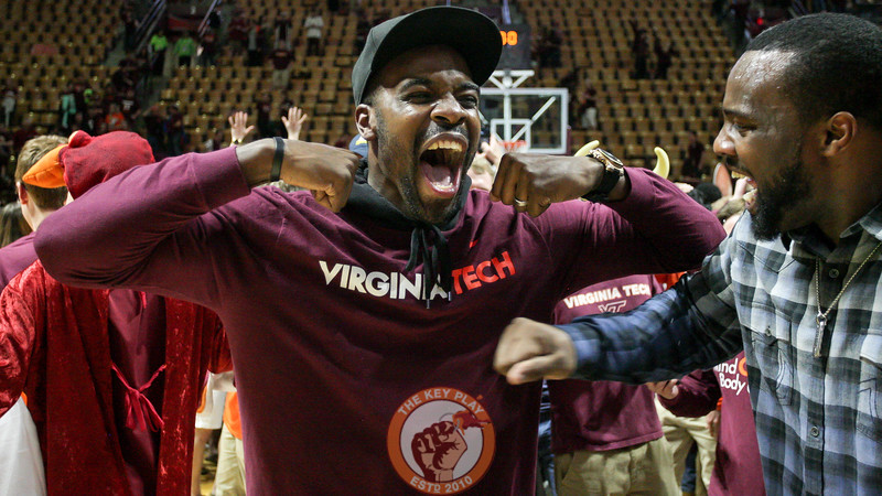 Former Virginia Tech basketball players Paul Debnam (left) and Dorenzo Hudson (right) celebrate on the court during the court storming. (Mark Umansky/TheKeyPlay.com)
