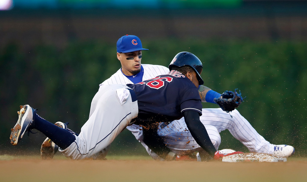 . Cleveland Indians\' Rajai Davis, front, dives back safely into second base on a pickoff attempt by Chicago Cubs\' Javier Baez during the second inning of a baseball game Wednesday, May 23, 2018, in Chicago. (AP Photo/Jim Young)