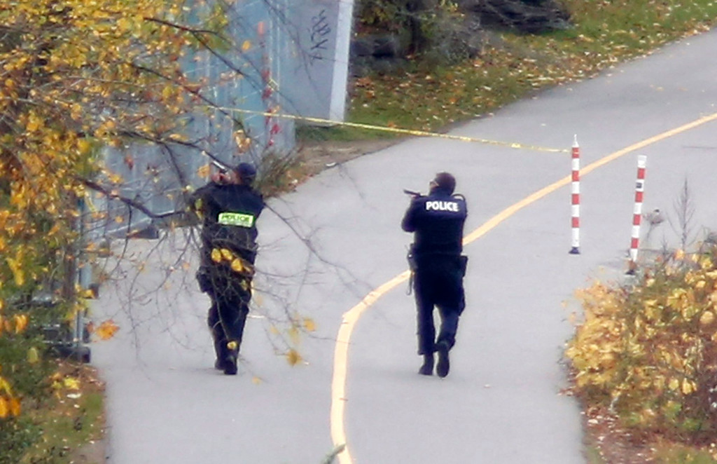 . Police search the bike path behind Parliament Hill  in Ottawa on  Wednesday, Oct. 22, 2014.  A Canadian soldier standing guard at a war memorial in the country\'s capital was shot to death and heavy gunfire then erupted inside Parliament. (AP Photo/The Canadian Press, Patrick Doyle)