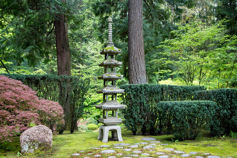 A stone pagoda between two trees.