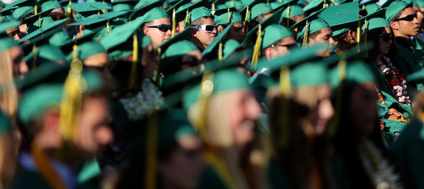 . A mass of green graduation caps sprawls across the Cabrillo College football field in Aptos on Friday evening as dozens of Harbor High seniors prepare to graduate. (Kevin Johnson/Sentinel)