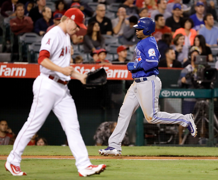 . Toronto Blue Jays\' Edwin Encarnacion, right, heads home to score on a sacrifice fly by Russell Martin off Los Angeles Angels starting pitcher Daniel Wright, left, during the fourth inning of a baseball game in Anaheim, Calif., Thursday, Sept. 15, 2016. (AP Photo/Chris Carlson)