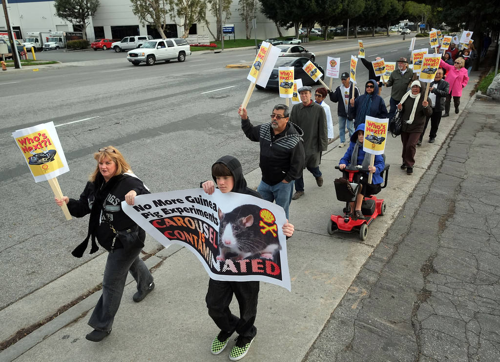 . Residents of the Carousel Tract neighborhood in Carson staged a protest against Shell Oil Friday by marching with signs from Dolphin Park to a Shell facility on Wilmington Avenue.  The protestors make their way to Shell along Wilmington Ave.. 20130308 Photo by Steve McCrank / Staff Photographer