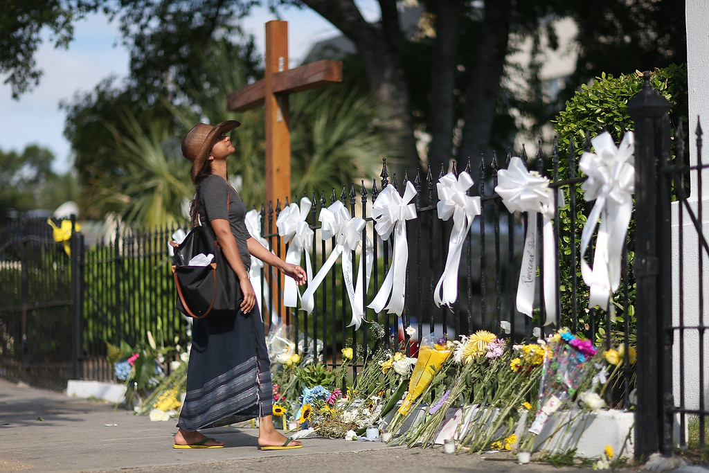 . Cindy Samaroo pays her respects in front of the Emanuel African Methodist Episcopal Church after a mass shooting at the church that killed nine people of June 19, 2015. A 21-year-old white gunman is suspected of killing nine people during a prayer meeting in the church, which is one of the nation\'s oldest black churches in Charleston. (Photo by Joe Raedle/Getty Images)