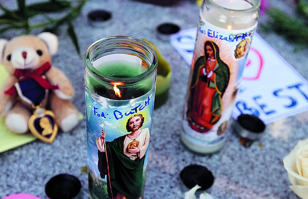 ". Memorial candles burn for Loran \""Butch\' Baker and Elizabeth Butler outside the Santa Cruz Police Department Wednesday. (Shmuel Thaler/Sentinel)"