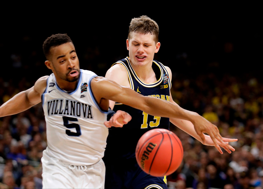 . Villanova guard Phil Booth (5) fights for a loose ball with Michigan forward Moritz Wagner during the second half in the championship game of the Final Four NCAA college basketball tournament, Monday, April 2, 2018, in San Antonio. (AP Photo/Eric Gay)