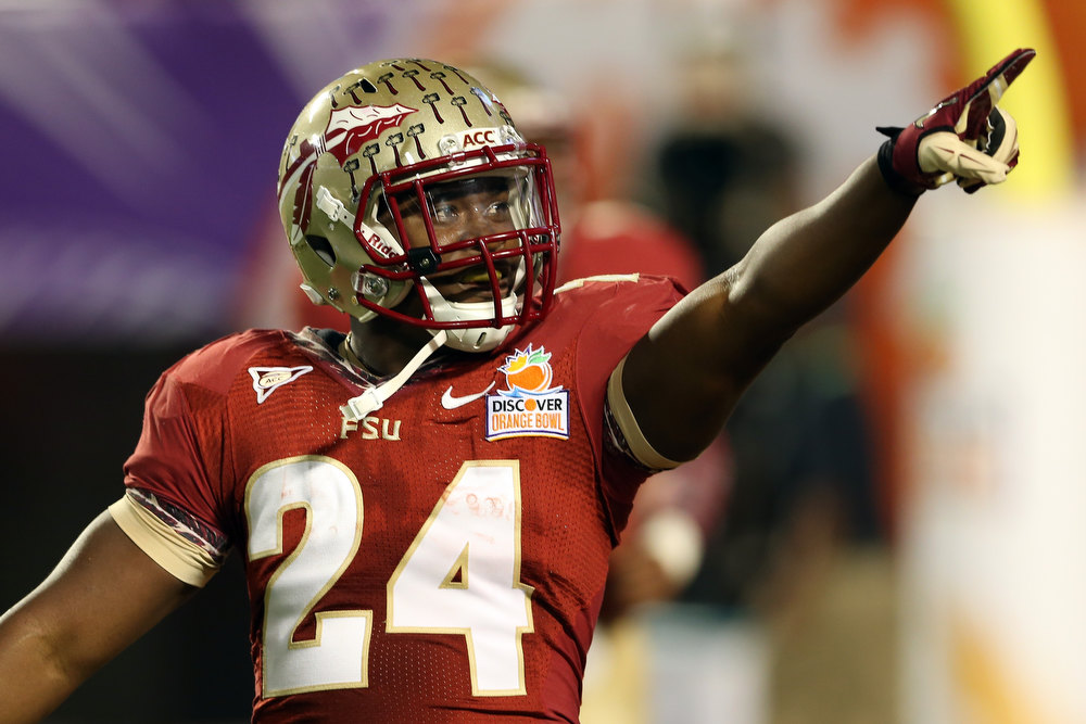 . Lonnie Pryor #24 of the Florida State Seminoles celebrates he scored a 60-yard rushing touchdown in the first quarter against the Northern Illinois Huskies during the Discover Orange Bowl at Sun Life Stadium on January 1, 2013 in Miami Gardens, Florida.  (Photo by Streeter Lecka/Getty Images)
