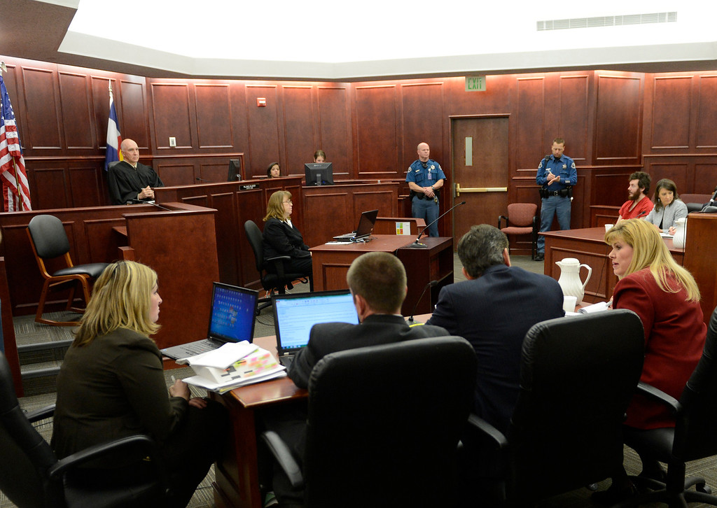 . Prosecutor Karen Pearson, dressed in red suit, and the prosecution team at their table during the proceedings where District Court Judge William Sylvester entered a Not Guilty plea on behalf of Holmes. The trial is set to begin August 5, 2013.  (Photo By RJ Sangosti/The Denver Post)