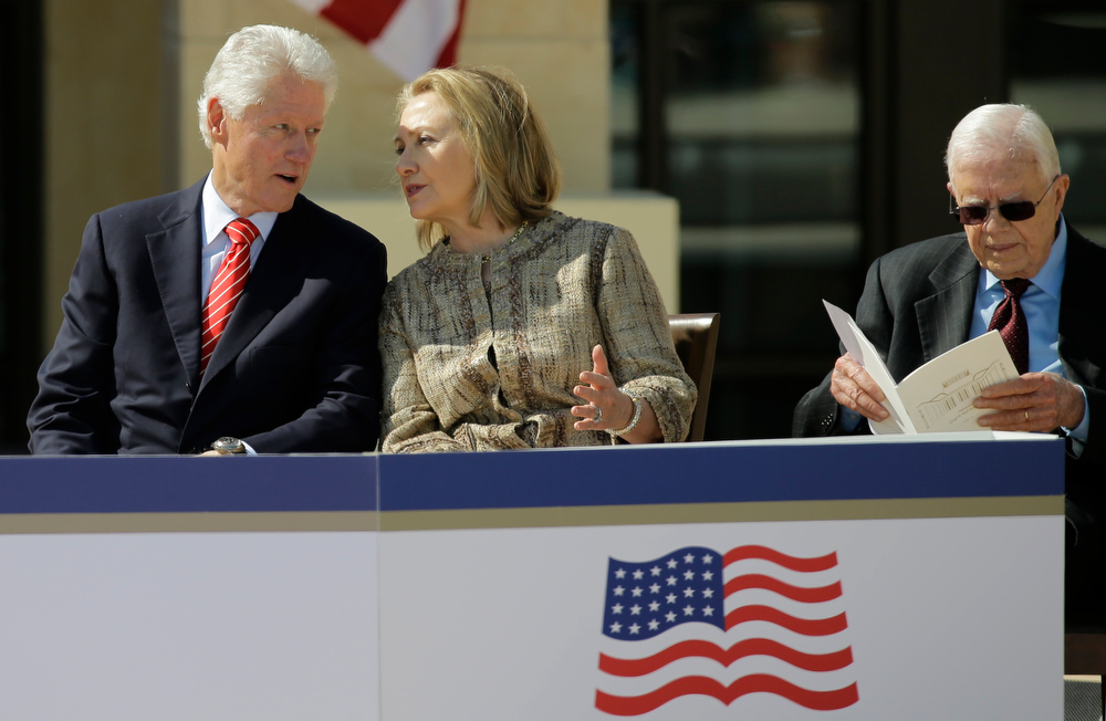 Description of . Former president William J. Clinton speaks with his wife former first lady Hillary Clinton during the dedication of the George W. Bush Presidential Center Thursday, April 25, 2013, in Dallas. At right is former president former president Jimmy Carter. (AP Photo/David J. Phillip)