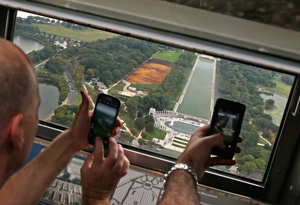 . Tourists make photographs from the Washington Monutment\'s observation deck of Cuban-American artist Jorge Rodriguez-Gerada\'s six-acre sand and soil \'facescape\' on the JFK Hockey Field along the north side of the Reflecting Pool on the National Mall October 1, 2014 in Washington, DC. (Photo by Chip Somodevilla/Getty Images)
