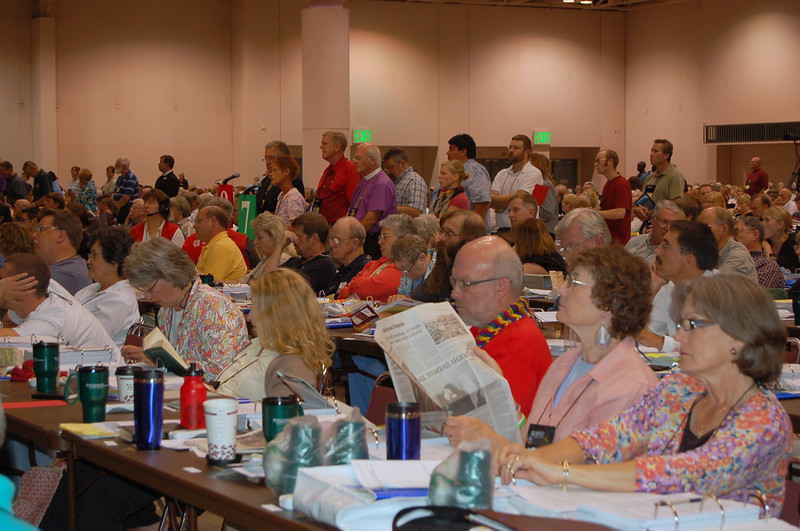 Reading the paper during a break in plenary session nine.